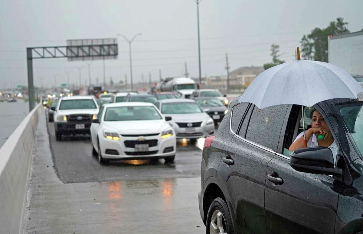 Jaylene Flores holds an umbrella as she sits in car with her mother, Elizabeth Castellanos, as they wait along the side of Sam Houston Tollway westbound between Wilson and Ralston Road near Garners Bayou on Sept. 19, 2019, in Houston.