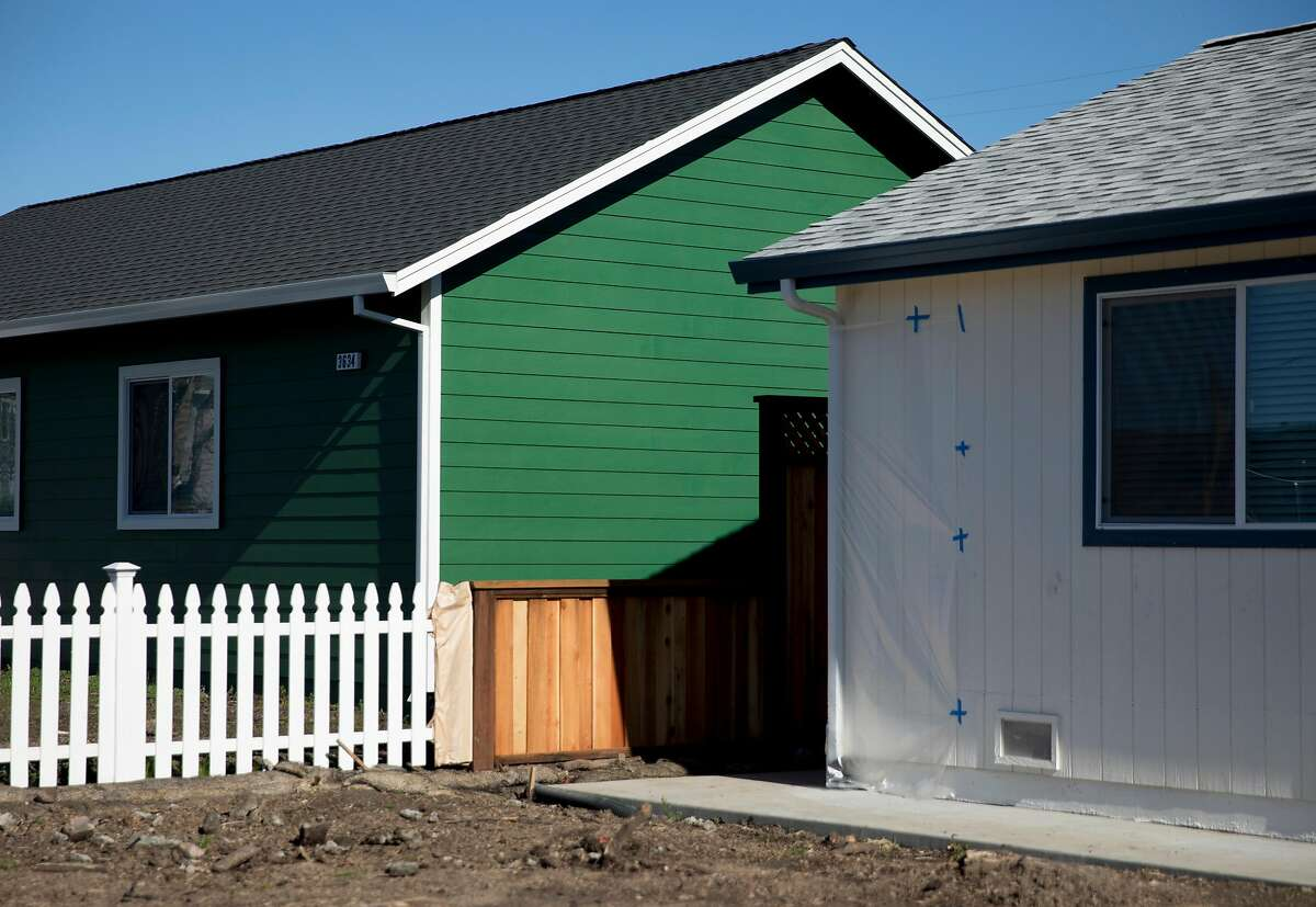 Two newly-constructed homes sit on a dirt lot along Coffey Lane in the Coffey Park neighborhood of Santa Rosa, Calif. Thursday, Jan. 24, 2019.