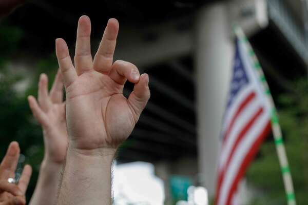 "(FILES) In this file photo taken on August 17, 2019 a far-right demonstrator makes the OK hand gesture believed to have white supremacist connotations during ""The End Domestic Terrorism"" rally at Tom McCall Waterfront Park on August 17, 2019 in Portland, Oregon. - The arrest of a US soldier with far-right sympathies who is suspected of plotting an attack on American soil to spark ""chaos"" has highlighted a challenge for the Pentagon: purging its ranks of extremists. Jarrett Smith, a private in the US Army based at Fort Riley in Kansas, was arrested and charged in federal court with one count of distributing information related to explosives after offering a detailed explanation to an undercover FBI agent.Smith also expressed interest in targeting members of the leftist group Antifa and heading to Ukraine to fight with a far-right paramilitary group, the FBI says. (Photo by John Rudoff / AFP)JOHN RUDOFF/AFP/Getty Images"