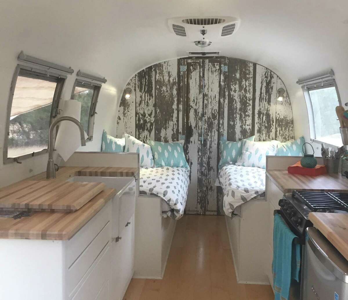 Mary Pat Mueller's restored 1966 Airstream trailer includes new twin beds and a farm sink, plus a new bathroom behind the pictured wall made from reclaimed farm wood.