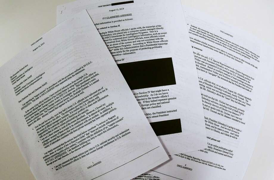 """Photo illustration on September 26, 2019 shows redacted pages of the whistleblower complaint referring to US President Donald Trump's call with his Ukrainian counterpart Volodymyr Zelensky. - Trump solicited interference from Ukraine to influence the 2020 US elections, and the White House intervened to """"lock down"""" the transcript of the call, the whistleblower said in a complaint released Thursday. """"I have received information from multiple US government officials that the president of the United States is using the power of his office to solicit interference from a foreign country in the 2020 US election,"""" the whistleblower, an unidentified intelligence community official, wrote in the complaint released by Congress. The whistleblower said White House officials had expressed alarm about the gravity of Trump's call with his Ukrainian counterpart, and that they told the whistleblower that they had likely """"witnessed the president abuse his office for personal gain."""" (Photo by EVA HAMBACH / AFP)EVA HAMBACH/AFP/Getty Images Photo: Eva Hambach, AFP/Getty Images"""