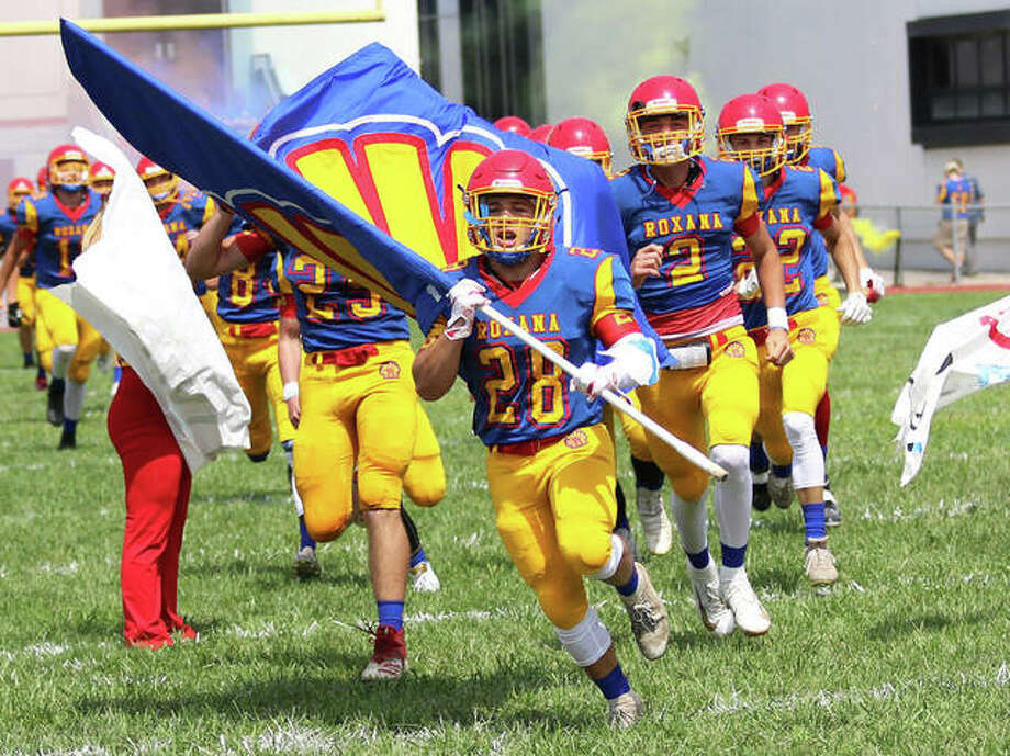 Roxana senior Michael Ilch (28) brings his team on the field while carrying the school's flag to open the 2019 season against Carlinville on Aug. 31. The Shells are back at Raich Field on Friday for a SCC game with Greenville. Photo: Greg Shashack | The Telegraph