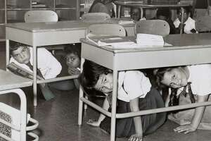 Students at a Brooklyn middle school have a 'duck and cover' practice drill in 1962 in preparation for a nuclear attack. From the New York World-Telegram archive.