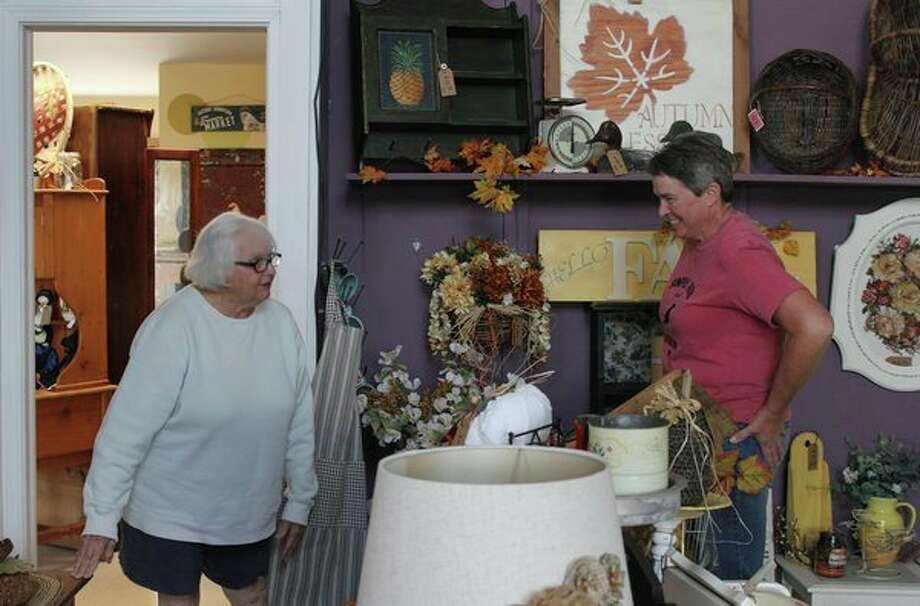 Diane Lentner, right, helps out a customer at Simply Prim and Farmhouse. She and Luann Blackstock opened the home decor store back in August. (Robert Creenan/Huron Daily Tribune)