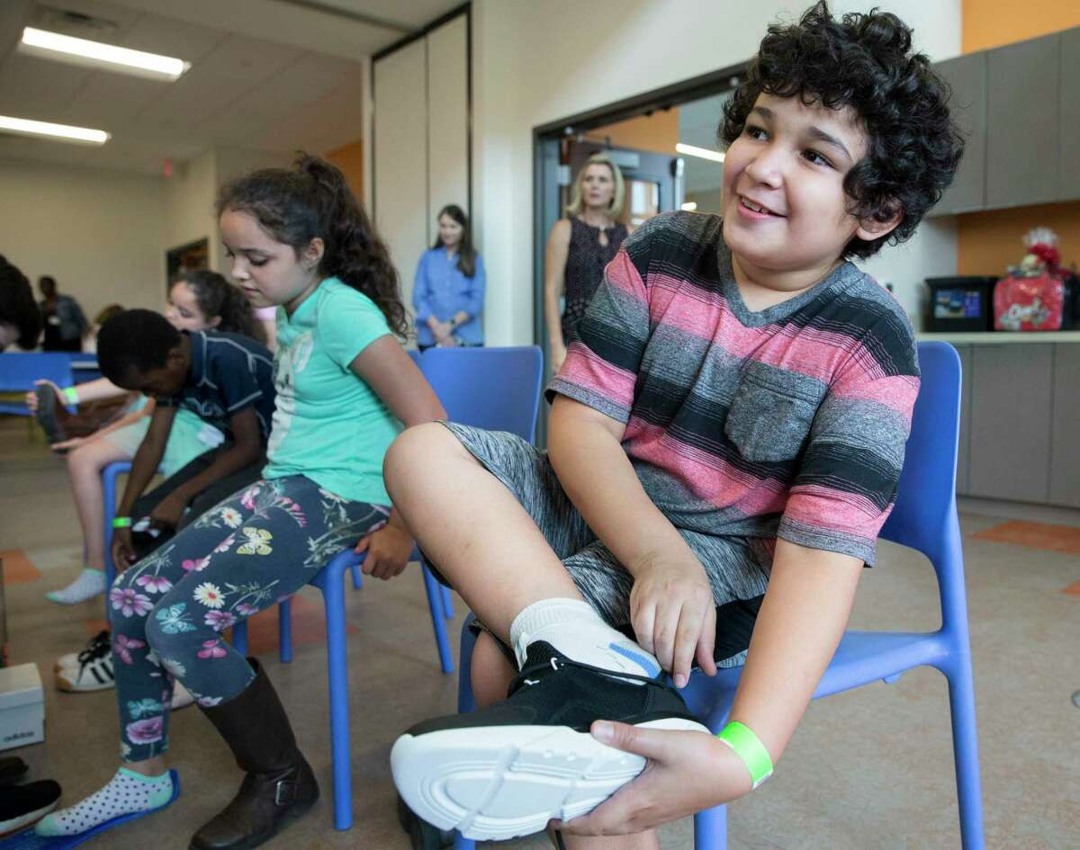 David Mahar, 11, tries on new shoes at the new Women & Family Development Center at Star of Hope's Cornerstone Community on Friday, Aug. 23, 2019, in Houston. More than 150 homeless children received a pair of shoes to start the 2019-2020 school year.