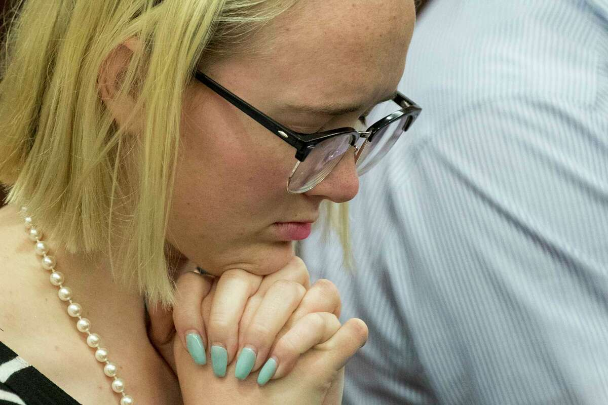 Cassidy Stay bows her head in prayer before Ronald Haskell was found guilty of capital murder in the shooting death of her parents on Thursday, Sept. 26, 2019, in Houston. Haskell was convicted of capital murder in connection with the 2014 massacre of a Spring family. Stay is the only survivor of the shooting, in which her parents and siblings were shot to death in their home.