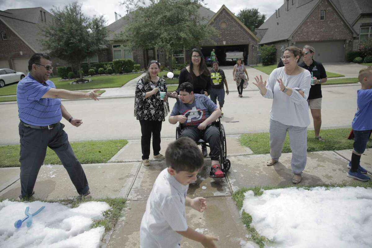 Rayyan Khan, center, and his family play in the snow in front of their Pearland home.