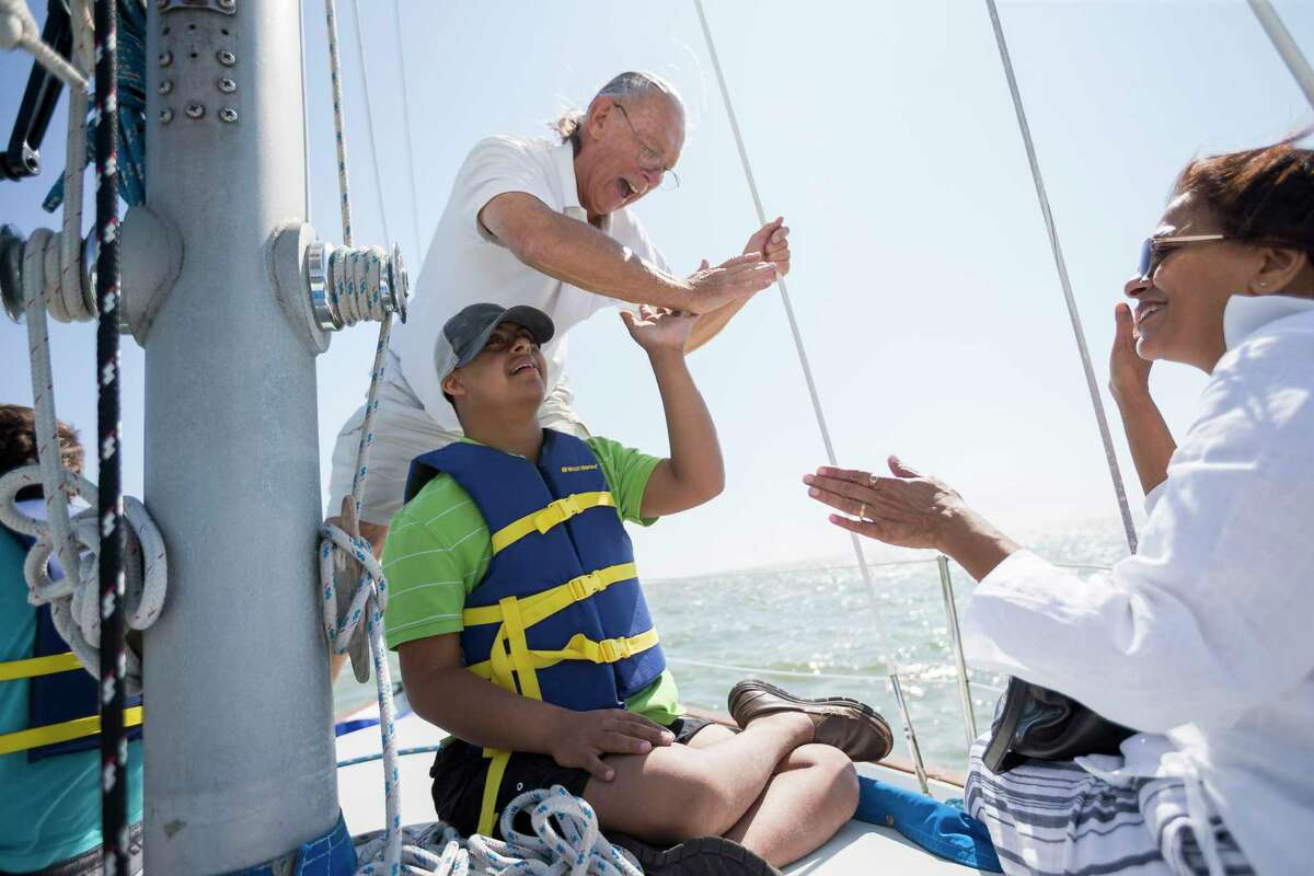 Rishi Trivedi, 17, high-fives Sailing Angels founder Dave McCabe after he helped set the main sail in Clear Lake, Thursday, July 25, 2019. Sailing Angels provides a sailing experience for children and adult with disabilities, takes out families