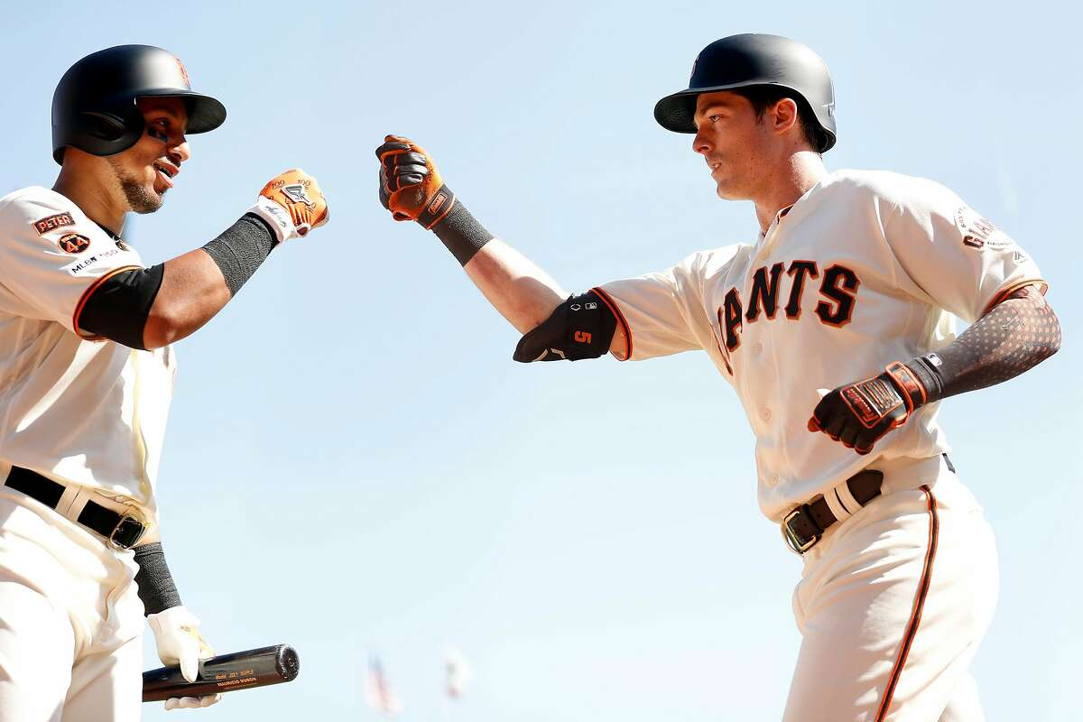 San Francisco Giants' Mike Yastrzemski fist bumps Cristhian Adames after his 4th inning home run against Colorado Rockies during MLB game at Oracle Park in San Francisco, Calif., on Thursday, September 26, 2019.