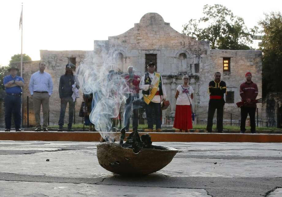 A local Native American group honored buried descendants during their 25th Annual Sunrise Ceremony at the Alamo on Saturday, Sept. 7, 2019. Ramon Juan Vasquez, executive director of American Indians in Texas at the Spanish Colonial Missions, along with over 60 people who many have ancestry with the Native Indians buried on the grounds of the Alamo, formed a circle in front of the church to pray and to honor their descendants. In the past, the group held the service inside the chapel but were told days before the event that the service would not be permitted inside the Alamo. With a noticeable presence of Alamo security officers and chains blocking the walkways to the front doors, the group formed a circle on Alamo Plaza to air their grievances and to remember their descendants. The group was joined by State Senator Jose Mendendez, State Rep. Leo Pacheco and Poet Laureate Carmen Tafolla who all expressed dismay that the indigenous group would not be allowed to pray and honor their loved ones inside the Alamo. Despite the prohibition, members of the Tap Pilam Coahuiltecan Nation and other indigenous people paid their respects on the ground by the front of the Alamo. A shell filled with sage slowly burned and filled the early morning sky with wafts of smoke - which traditionally serves to bless and purify - as the service ended as the sun slowly rose over the Alamo. (Kin Man Hui/San Antonio Express-News) Photo: Kin Man Hui, Staff Photographer