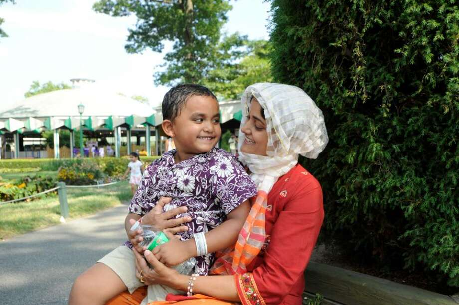 Jolly Miru holds her son, Mustfiq, 4, taking a break at Playland, in Rye, N.Y., on Thursday, Aug. 5, 2010.  The Miru family is originally from Bangladesh. Westchester County is looking into closing Playland, which hasn't posted a profit in decades. Photo: Helen Neafsey / Greenwich Time