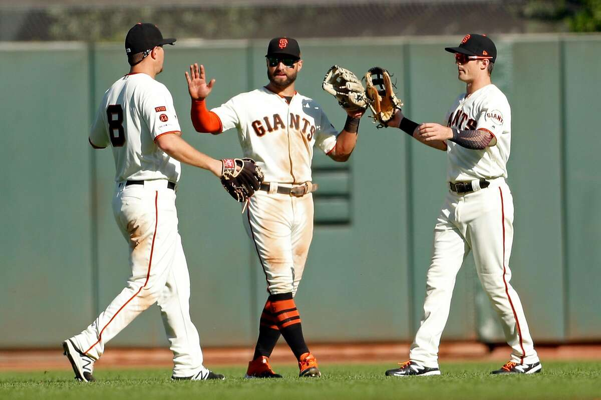 Giants' Alex Dickerson, Kevin Pillar and Mike Yastrzemski greet each other after 8-3 win over Colorado at Oracle Park in San Francisco, September 26, 2019.