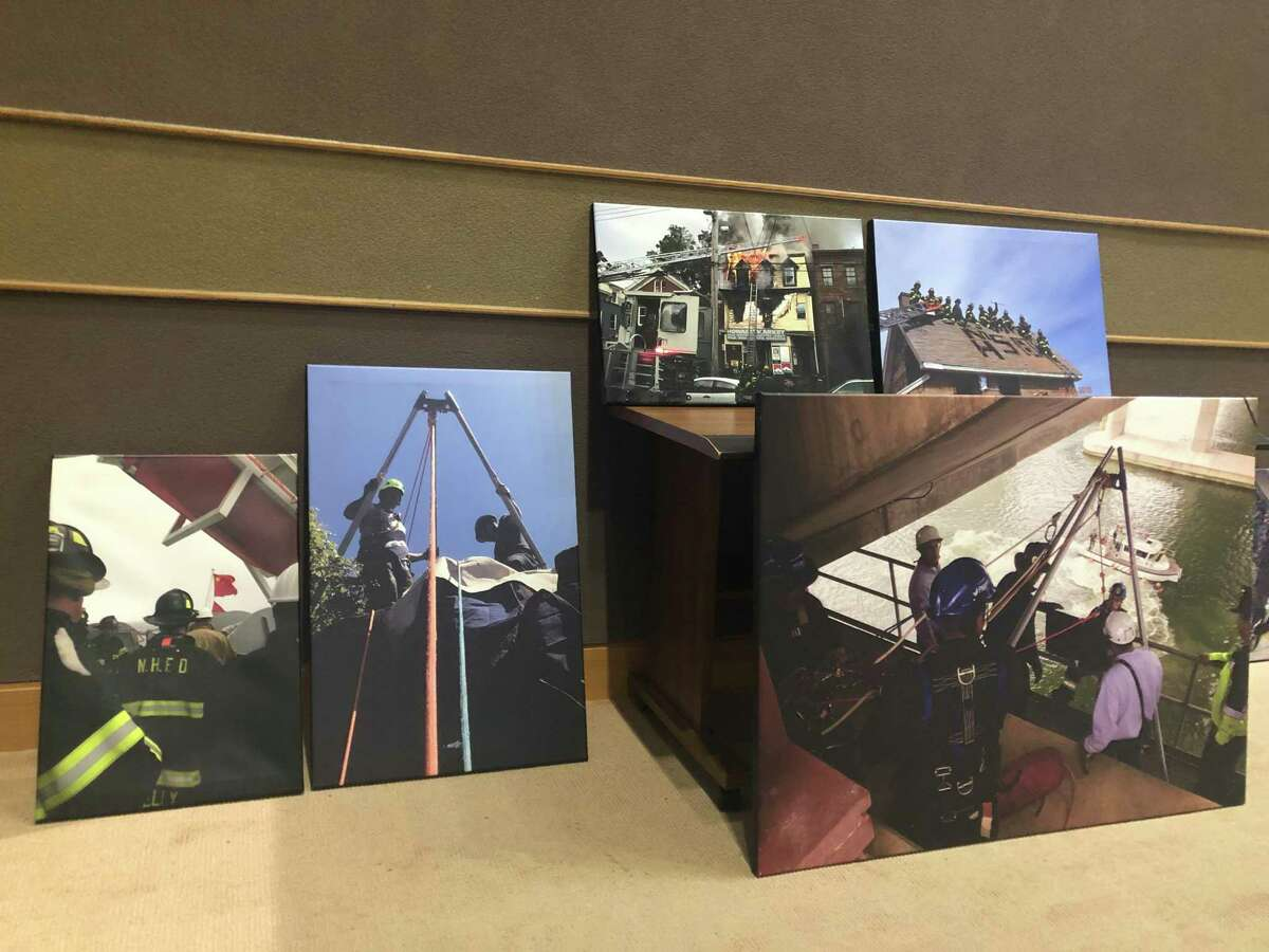 The Board of Alders Finance Committee considered and passed the potential contract for city firefighters onto the full body Thursday evening. Here, photos brought and displayed by the firefighters.