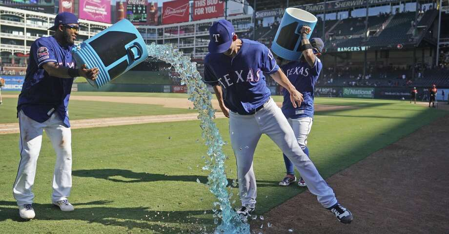 Texas Rangers shortstop Elvis Andrus, left, tries to pour sports drink over starting pitcher Mike Minor, right front, who dodges the effort, after the team's 7-5 win over the Boston Red Sox on Thursday, Sept. 26, 2019, in Arlington, Texas. (AP Photo/Louis DeLuca) Photo: Louis DeLuca/Associated Press