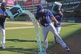 Texas Rangers shortstop Elvis Andrus, left, tries to pour sports drink over starting pitcher Mike Minor, right front, who dodges the effort, after the team's 7-5 win over the Boston Red Sox on Thursday, Sept. 26, 2019, in Arlington, Texas. (AP Photo/Louis DeLuca)