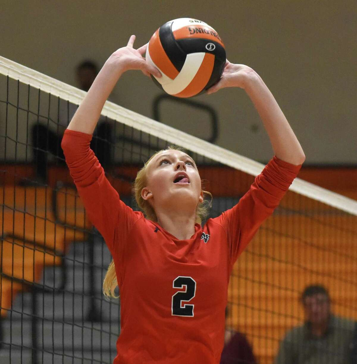 New Canaan's Elle Sneddon sets the ball during a volleyball match between New Canaan and Stamford at Stamford High School.