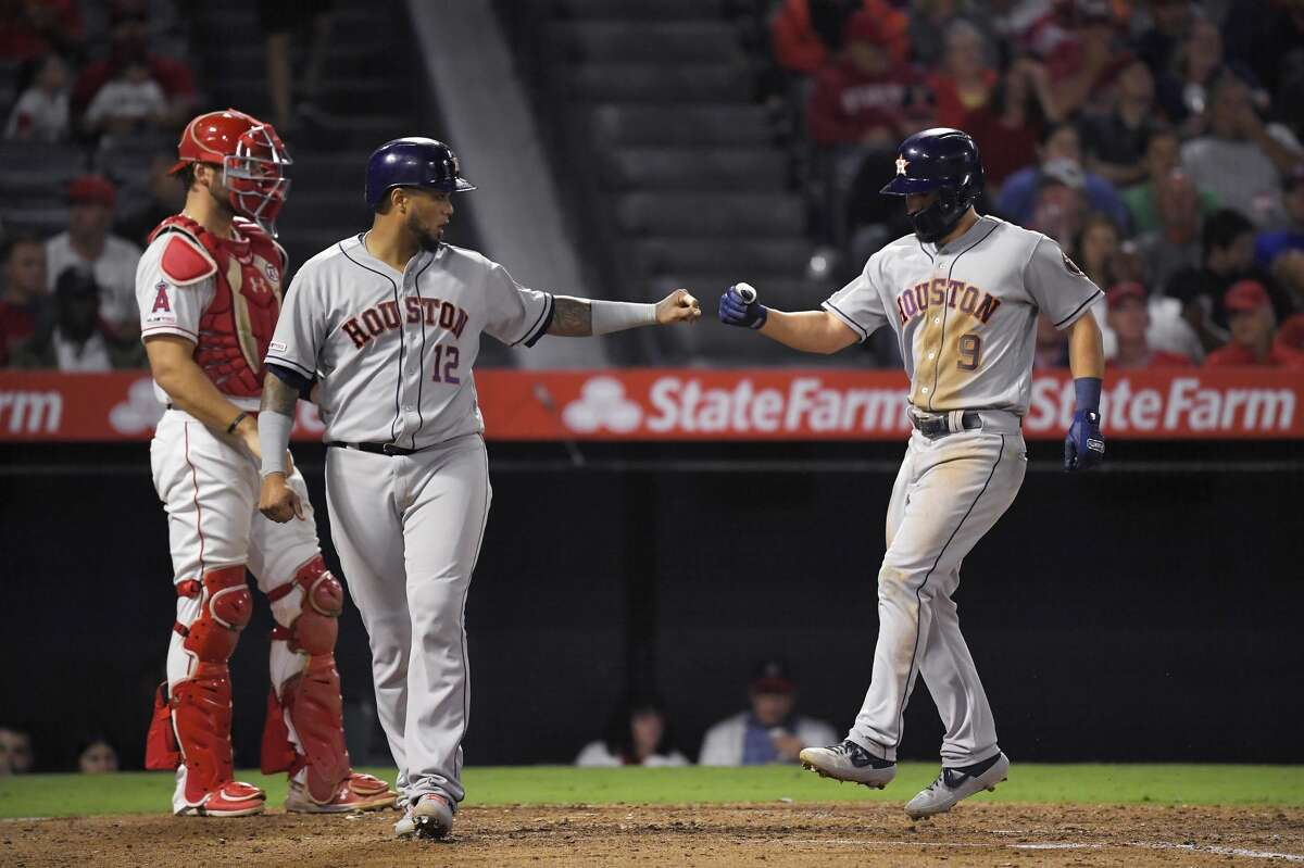 Houston Astros' Jack Mayfield, right, is congratulated by Martin Maldonado, center, after hitting a two-run home run, while Los Angeles Angels catcher Kevan Smith stands at the plate during the fifth inning of a baseball game Thursday, Sept. 26, 2019, in Anaheim, Calif. (AP Photo/Mark J. Terrill)