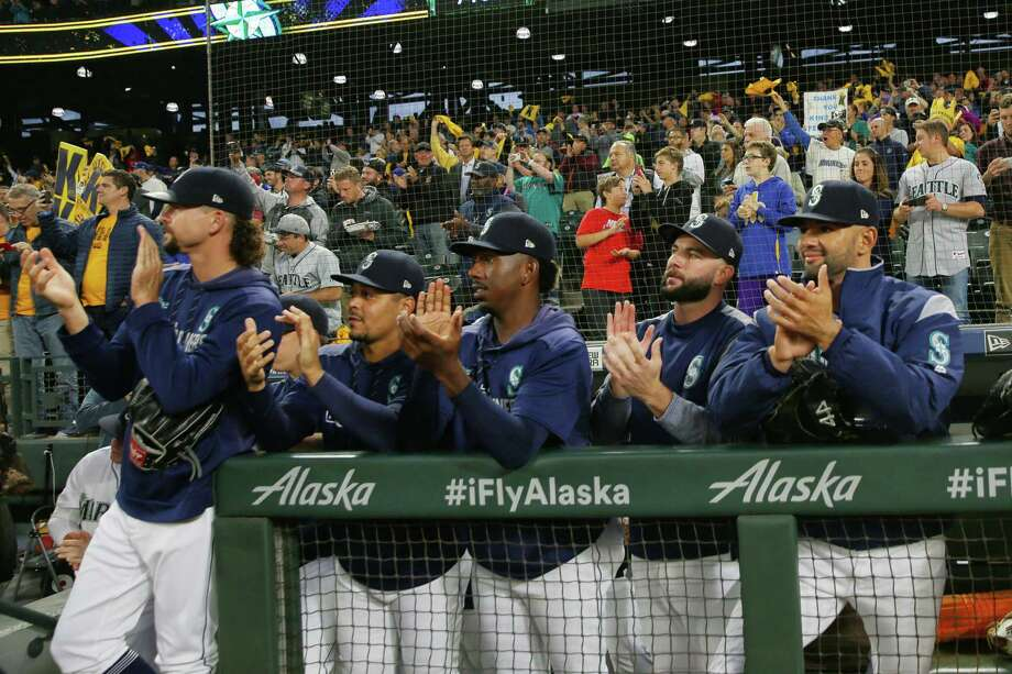 Seattle Mariners players clap for starting pitcher Felix Hernandez as walks across the field for what is likely his final start in their game against the Oakland Athletics, Thursday, Sept. 26, 2019. Photo: Genna Martin, Seattlepi.com / GENNA MARTIN