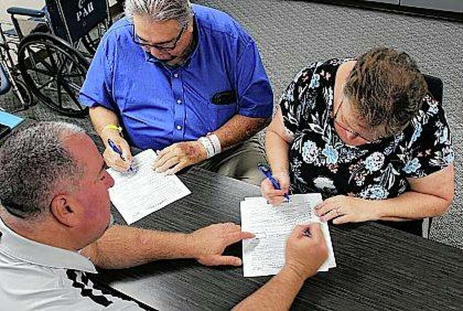 James Leeds and his wife, Joanne, sign paperwork to close on their new house while at Passavant Area Hospital. When a hospitalization threatened to derail the couple's home-buying process, a banker and medical staff members stepped in. Photo: Photo Provided