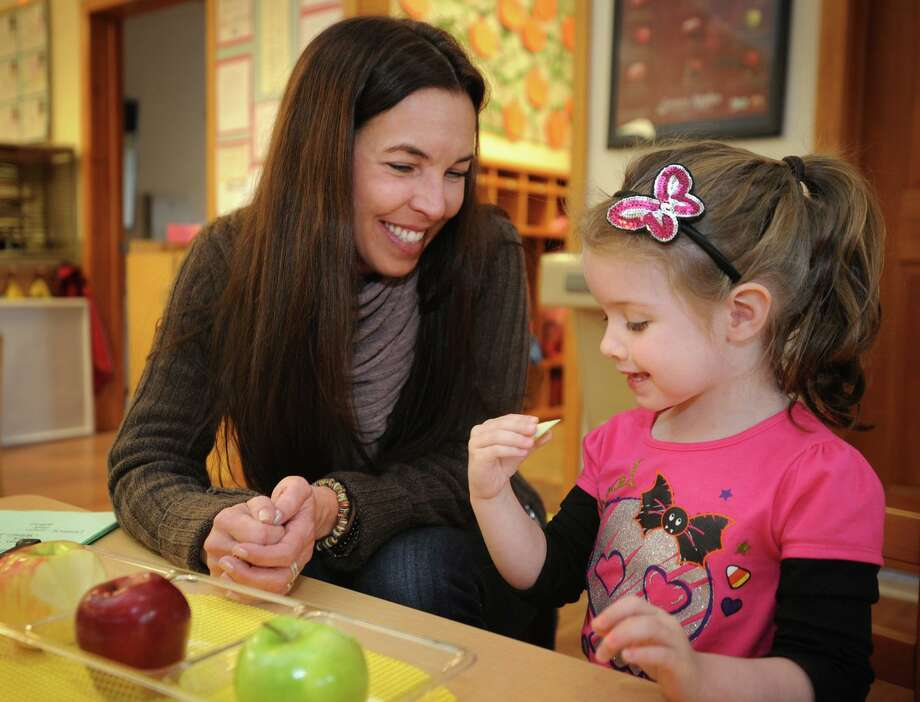 Director and head teacher Jacqueline Lema conducts an apple tasting activity with student Delaney at the nature-based Redwing Pond House Preschool in Ansonia, Conn. on Wednesday, October 30, 2013. Photo: Brian A. Pounds / Brian A. Pounds / Connecticut Post