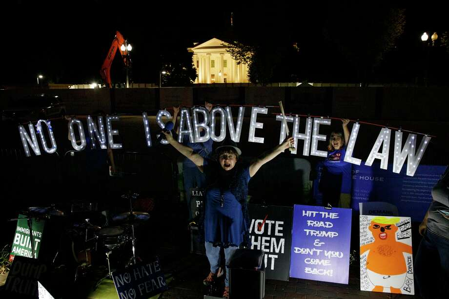 "Protesters with Kremlin Annex with a light sign that reads ""NO ONE IS ABOVE THE LAW"" call to impeach President Donald Trump in Lafayette Square Park in front of the White House in Washington, Thursday, Sept. 26, 2019. Photo: Carolyn Kaster / Associated Press / Copyright 2019. The Associated Press. All rights reserved."