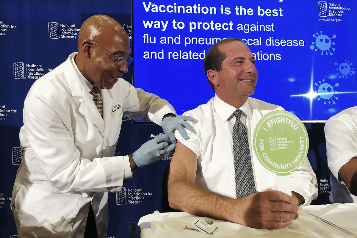 B.K. Morris, a nurse with MedStar Visiting Nurses Association, gives a flu shot to Secretary of Health and Human Services Alex Azar during a news conference in Washington. The flu forecast is cloudy and it's too soon to know if the U.S. is in for a third miserable season in a row, but health officials said Thursday, Sept. 26, 2019, not to delay vaccination. (AP Photo/Lauran Neergaard)