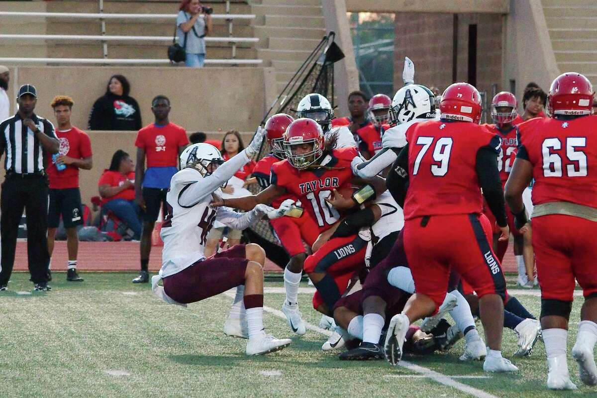 Alief Taylor's Esteban Torres (10) is wrestled down by a crowd of Pearland defenders Thursday at Crump Stadium.