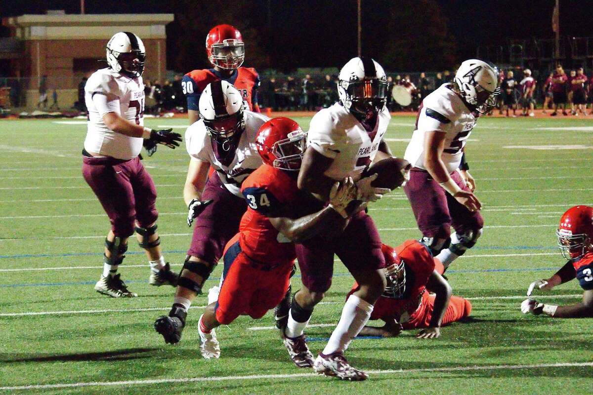Pearland's Brandon Campbell (7) drags Alief Taylor's Everett Haven (34) into the end zone Thursday at Crump Stadium.