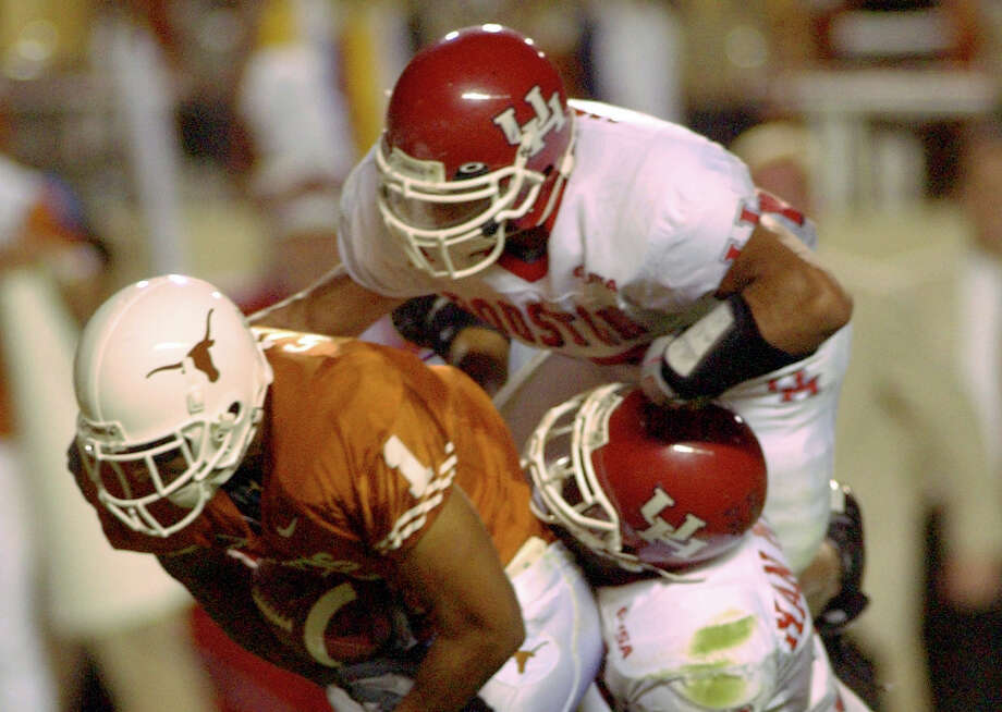 PHOTOS: UH vs. Tulane  Texas receiver Sloan Thomas drags Houston's Victor Malone (top) and Jermain Woodard towards the goal line on his way to scoring another touchdown late in the second quarter Saturday night at Darrell K. Royal - Texas Memorial Stadium in Austin, Texas.             9/21/02              Karl Stolleis/Houston Chronicle.      HOUCHRON CAPTION (09/24/2002): Trying to stop Sloan Thomas was kind of a drag for UH defenders like Victor Malone, top, and Jermain Woodard as Thomas caught six passes for 87 yards and a touchdown against the Cougars. >>>See photos from the Cougars' game against Tulane last week ...  Photo: Karl Stolleis/Houston Chronicle