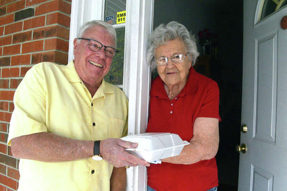 "Evelyn, right, who is 96, has lunch delivered on Thursday by Edwardsville alderman Jack Burns as part of the ""Big Wheels Deliver Meals"" program at Main Street Community Center in Edwardsville. Photo: Scott Marion/The Intelligencer"