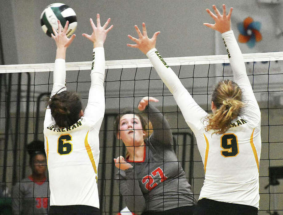 Alton's Olivia Ducey (middle) hits into the block put up by Metro-East Lutheran's Anne Kienle and Caitlyn Reynolds (9) in a Redbirds' win Aug. 28 at Hooks Gym in Edwardsville. Ducey and the Redbirds were at home Thursday night and dropped a three-set battle with Belleville West. Photo: Matt Kamp / Hearst Illinois