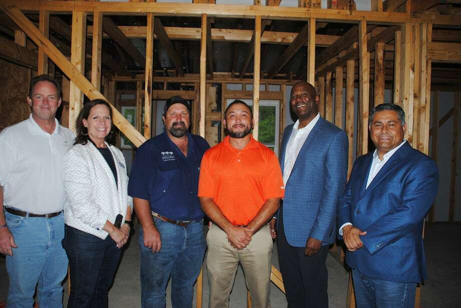 From left: Patrick Mayhan, president of HomeAid; Carole Brady, executive director of HomeAid; Quintes Stark, chief operations and facilities officer for Boys and Girls Country; Rafael Casas, construction manager with Empire Homebuilding; James Miller, regional president for Empire Homebuilding and Vincent Duran, executive director Boys and Girls Country join other guests at the cottage under construction to write inspirational notes on the structure's frame.