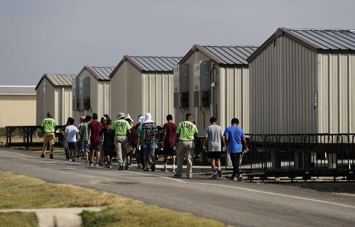 FILE - In this July 9, 2019, file photo, staff escort immigrants to class at the U.S. government's newest holding center for migrant children in Carrizo Springs, Texas. The Trump administration will make a case in court to end a longstanding settlement governing detention conditions for immigrant children, including how long they can be held by the government. A hearing is scheduled before a federal judge Friday, Sept. 27, in Los Angeles over the so-called Flores settlement. (AP Photo/Eric Gay, File)