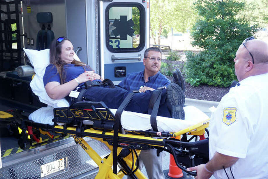 EMS manager Jason Bowman, center, and squad leader Jared Brooks lift paramedic Meghan Osterbur on a power stretcher during a demonstration of the new Duck Pluckers ambulance at Alton Memorial Hospital.