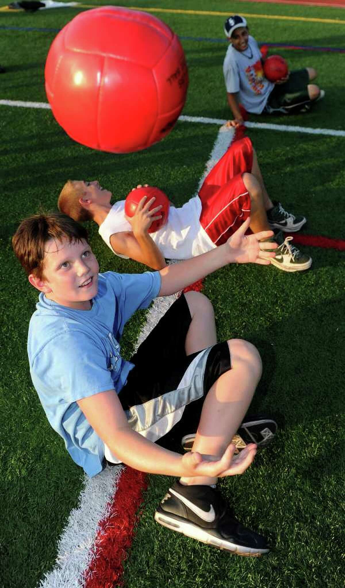 Ryan Holbrook, 11, practices a fitness drill during the Chelsea Cohen Fitness Academy Kickoff at Norwalk High School's Testa Field on Thursday, August 5, 2010.