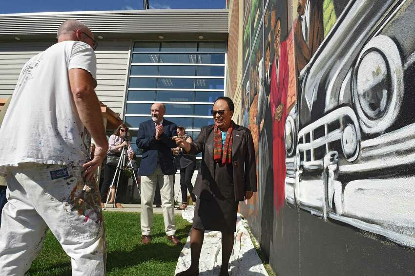 Rensselaer Polytechnic Institute President Shirley Ann Jackson, right, hands a paintbrush back to mural artist Kevin Clark, left, after she put the finishing touches on his mural he painted on the Hedley/River Street Market building on Friday, Sept. 27, 2019 in Troy, N.Y. Jackson is represented in the mural. The mural is a tribute to Troy and shows the building how it used to look like back when it was an Arrow shirt factory. (Lori Van Buren/Times Union)