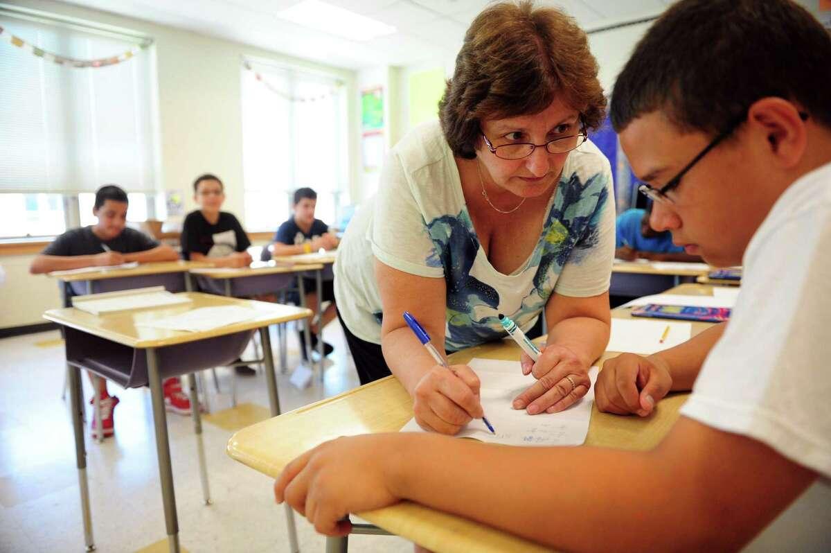 Evelyn Maru helps eighth grade student Daniel Arguedas with a math problem during summer school Thursday, July 12, 2012 at Cesar Batalla School in Bridgeport, Conn.