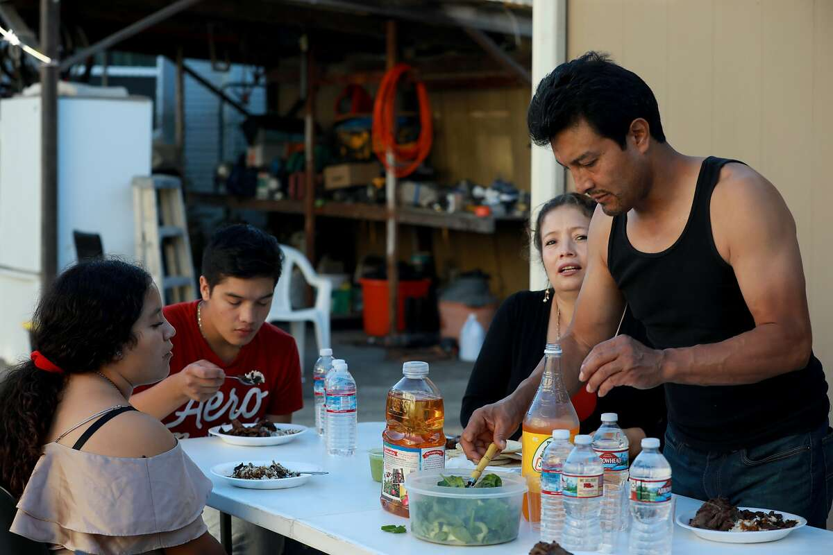 Alexa Lopez, 16, Dennis Lopez, 18, Dianeth Lopez, 39, and Raul Lopez, 47, prepare to have dinner at their home in Richmond, Calif., on Tuesday, September 24, 2019. The elder Lopez is an undocumented immigrant who was detained by ICE for 2 years before being released in February.