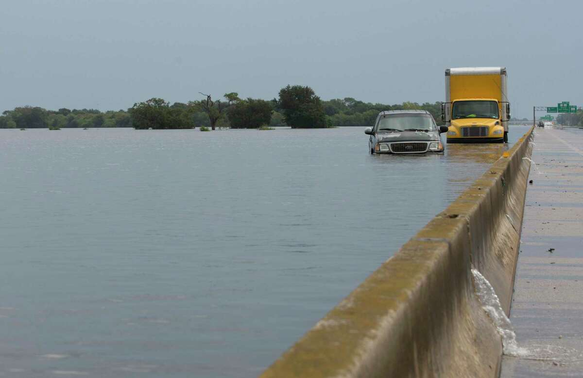 Abandoned vehicles sit in the flood water from Tropical Depression Imelda on Interstate Highway 10 westbound lanes on Friday, Sept. 20, 2019, in Winnie. I-10 remains closed between Texas Highway 61 and Winnie.