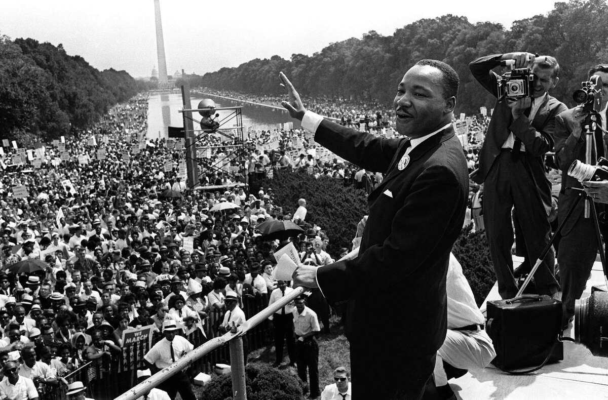 This August 28, 1963 file photo shows US civil rights leader Martin Luther King (C) waving from the steps of the Lincoln Memorial to supporters on the Mall in Washington, DC, during the