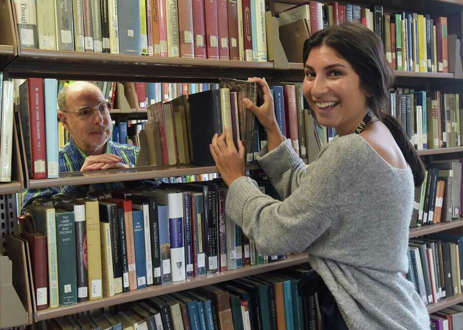 """WCSU Access Services Librarian Russ Gladstone (left), who posed recently in the Haas Library stacks with nursing student and library assistant Katie Schmidt, will be among the university and community volunteers who will serve as """"human books"""" for the Human Library event on Oct. 1. Gladstone's """"book"""" will be titled, """"Union Advocate."""" Photo: Contributed Photo / Contributed / The News-Times Contributed"""