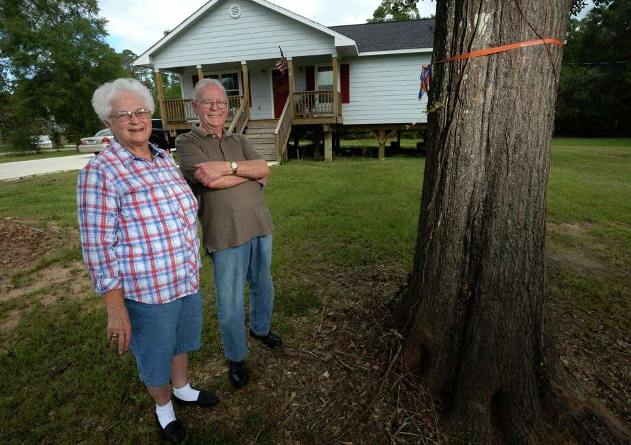 In designing her post Tropical Storm Harvey home in Bevil Oaks, Orvalee Husband said she told her contractor to build it above the orange rope tied around a front-yard tree which marks the water level after Harvey. Arman Husband is also pictured. Photo taken Friday, 9/27/19 Photo: Guiseppe Barranco/The Enterprise, Photo Editor / Guiseppe Barranco ©