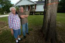 In designing her post Tropical Storm Harvey home in Bevil Oaks, Orvalee Husband said she told her contractor to build it above the orange rope tied around a front-yard tree which marks the water level after Harvey. Arman Husband is also pictured. Photo taken Friday, 9/27/19