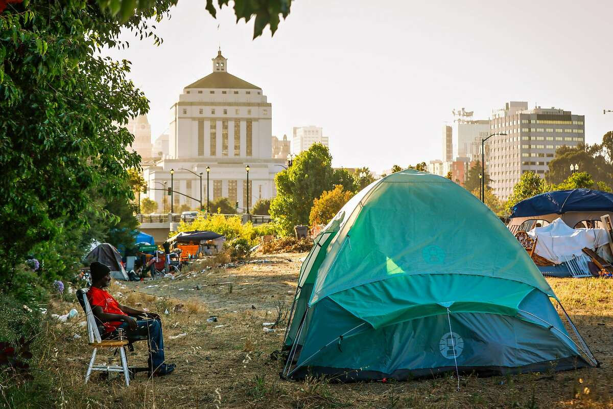 Ollie Harris, 69, sits outside his tent at an encampment on East 12th Street in Oakland, California, on Wednesday, July 24, 2019. Ollie and his partner Debbie are currently homeless. They went through Oakland's Tuff Shed program where they resided before getting permanent housing in Stockton. After spending a month in an apartment in Stockton the couple moved back to an encampment in Oakland because they claimed the apartment was infested with rats and cockroaches.