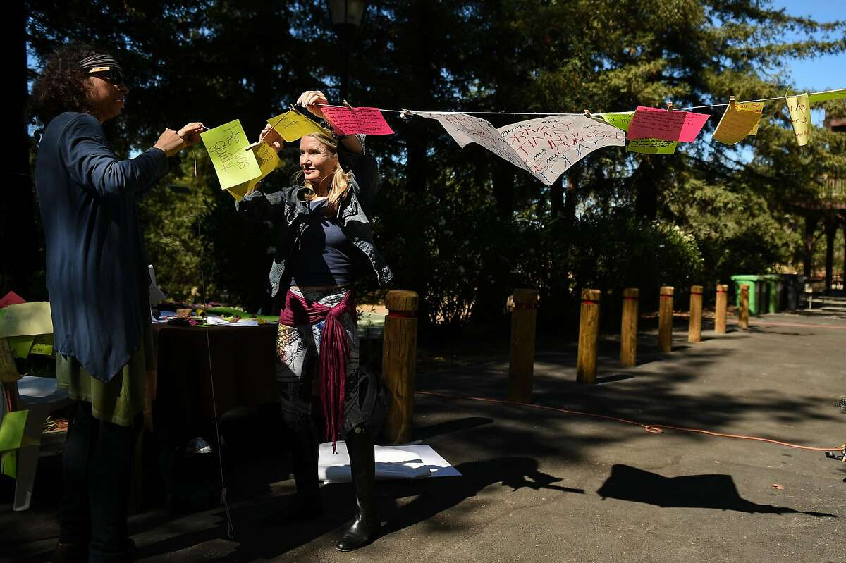 Sandra Schachat, left, a Stanford PhD geological sciences student from New York City, left, and Jennifer Jones-Schroeder, mother of co-organizer Hope Schroeder, the Stanford grad who helped start an augmented reality experience near the site of a sexual assault near a student housing complex off Lomita Drive on the campus of Stanford University, hang colorful messages of support for the victim on Friday September 27, 2019.