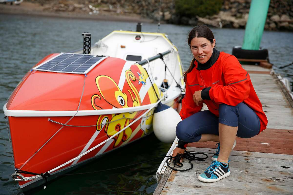 Long-distance ocean rower Lia Ditton kneels for a portrait with her boat at Travis Marina on Friday, September 27, 2019 in Sausalito, CA.