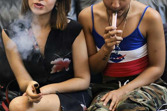 FILE - In this Saturday, June 8, 2019 file photo, two women smoke cannabis vape pens at a party in Los Angeles. On Friday, Sept. 27, 2019, the Centers for Disease Control and Prevention said more than three-quarters of the 805 confirmed and probable illnesses from vaping involved THC, the ingredient that produces a high in marijuana. (AP Photo/Richard Vogel)
