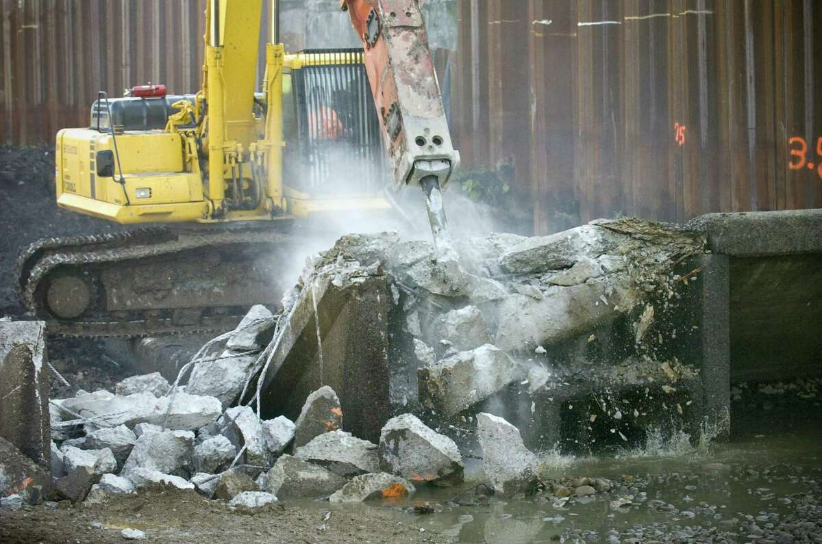 workers demolish the dam in Mill River Park in Stamford on Tuesday, Sept. 29, 2009.