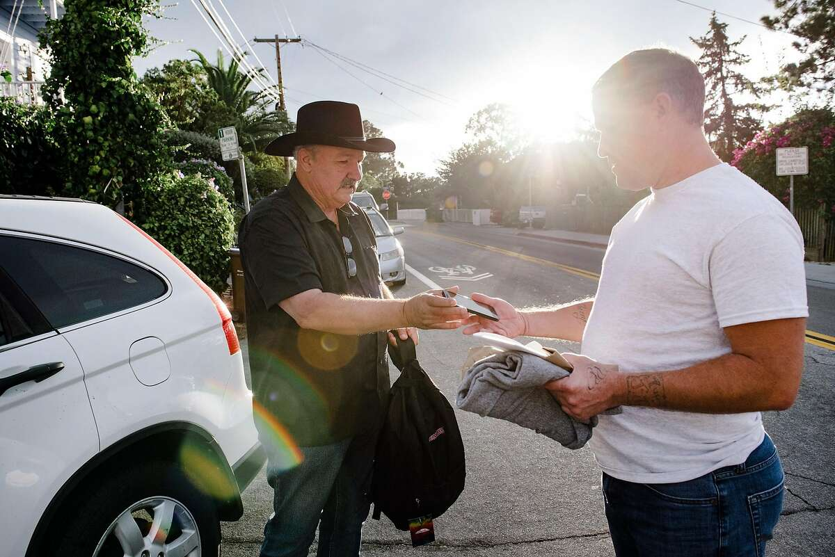 Marvin Mutch, left, director of advocacy for Prisoner Reentry Network, hands Billy Jordan a new cellphone donated in a care package by Bonifidelife.org, as he is released after serving 3 years for robbery, including one year at San Quentin State Prison, in San Quentin, Calif, on Friday, September 27, 2019.