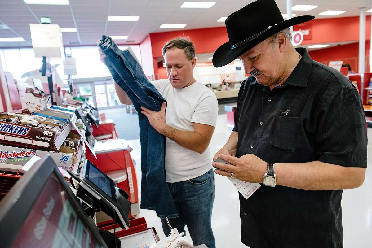 Marvin Mutch, right, director of advocacy for Prisoner Reentry Network, pays for a new set of clothing for Billy Jordan after his release from San Quentin State Prison where he served 1 of his 3 year sentence for robbery, in San Rafael, Calif, on Friday, September 27, 2019.
